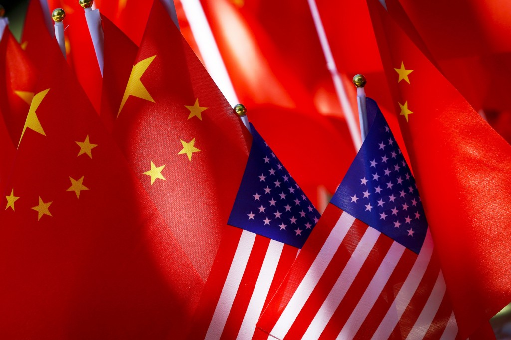 FILE - In this Sept. 16, 2018, file photo, American flags are displayed together with Chinese flags on top of a trishaw in Beijing. China says Friday,...
