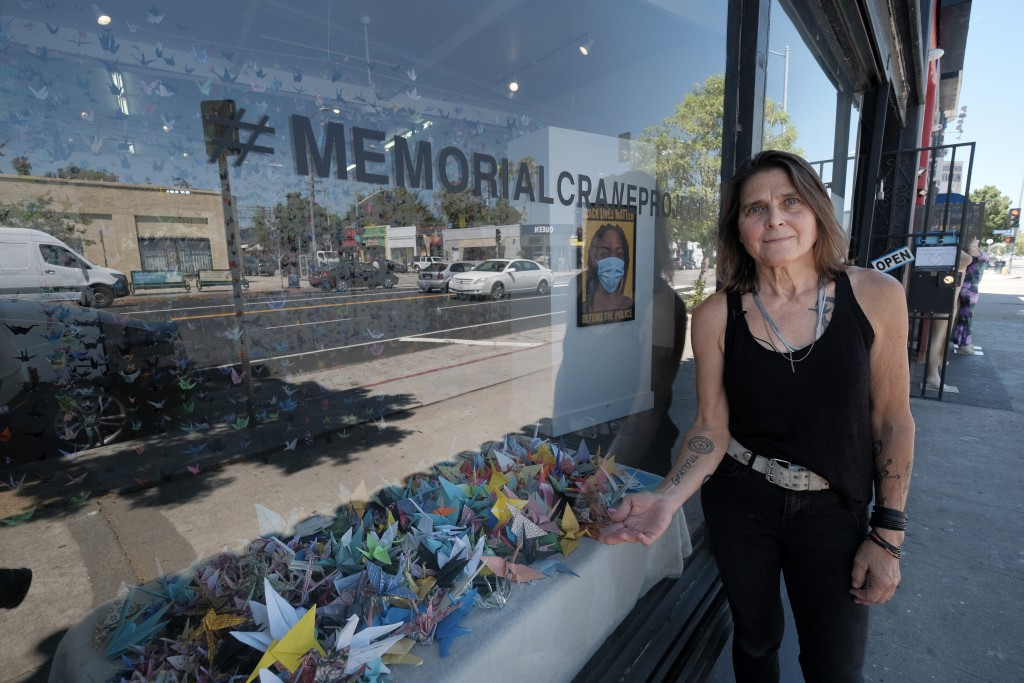 """Artist Karla Funderburk, owner of Matter Studio Gallery, poses outside her gallery displaying a window of origami paper cranes during an exhibit """"Hono..."""