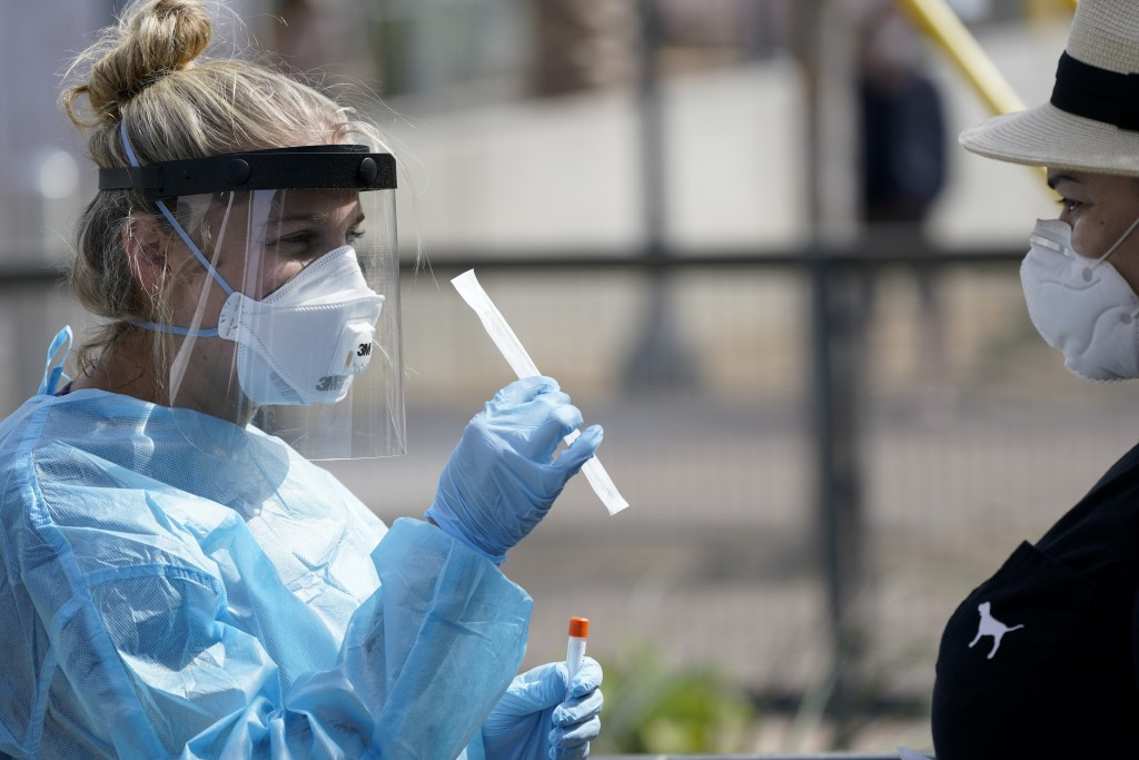 Nurse practitioner Debbi Hinderliter, left, collects a sample from a woman at a coronavirus testing site near the nation's busiest pedestrian border c...