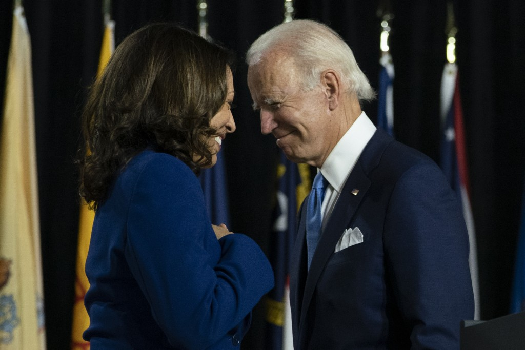 Democratic presidential candidate former Vice President Joe Biden and his running mate Sen. Kamala Harris, D-Calif., pass each other as Harris moves t...