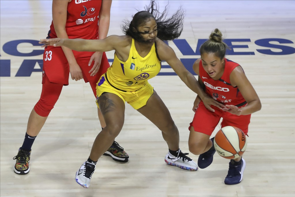 Washington Mystics' Leilani Mitchell, right, dribbles past the defense of Los Angeles Sparks' Te'a Cooper during the first half of a WNBA basketball g...