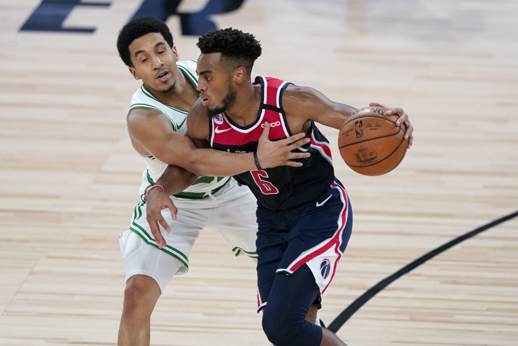 Washington Wizards' Troy Brown Jr. (6) brings the ball down the court as Boston Celtics' Tremont Waters defends during the second half of an NBA baske...
