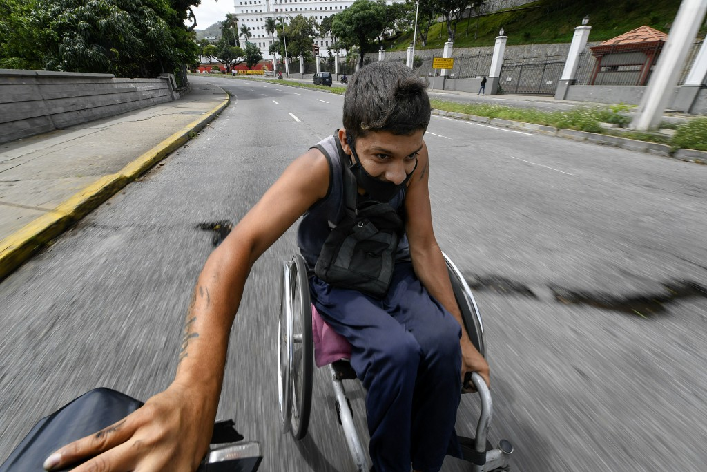A man wearing a protective face mask hitches a ride in his wheelchair by grabbing on to the back of a motorcycle, near the Miraflores Palace in Caraca...