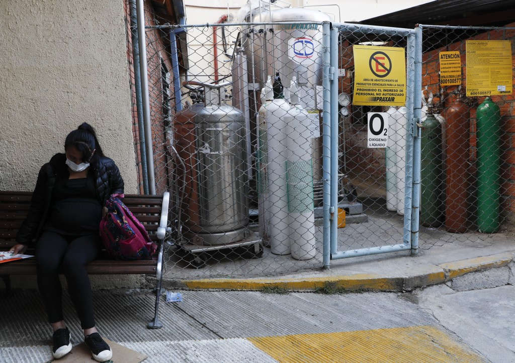 A pregnant woman waiting to be attended sits on a bench situated next to an oxygen tank storage area, outside the Women's Hospital, in La Paz, Bolivia...