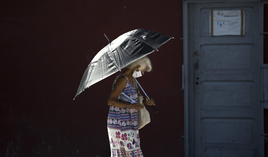A pedestrian wearing a face mask amid the new coronavirus uses a parasol in Havana, Cuba, Monday, Aug. 10, 2020. Cuban authorities on Monday re-impose...