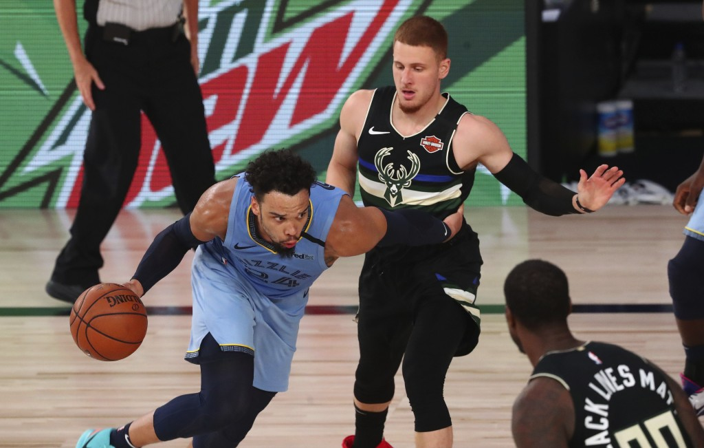 Memphis Grizzlies guard Dillon Brooks (24) drives against Milwaukee Bucks guard Donte DiVincenzo, top right, in the first half of an NBA basketball ga...