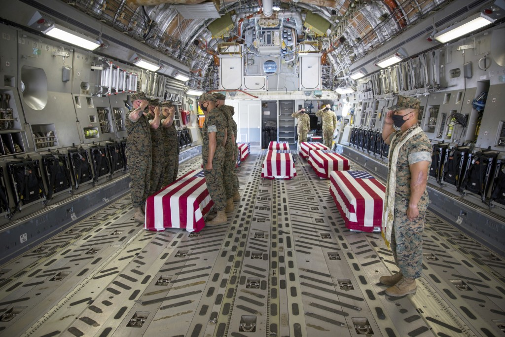 U.S. Marines and sailors render a final salute to the fallen inside a U.S. Air Force C-17 Globemaster III at Marine Corps Air Station Miramar, in Cali...