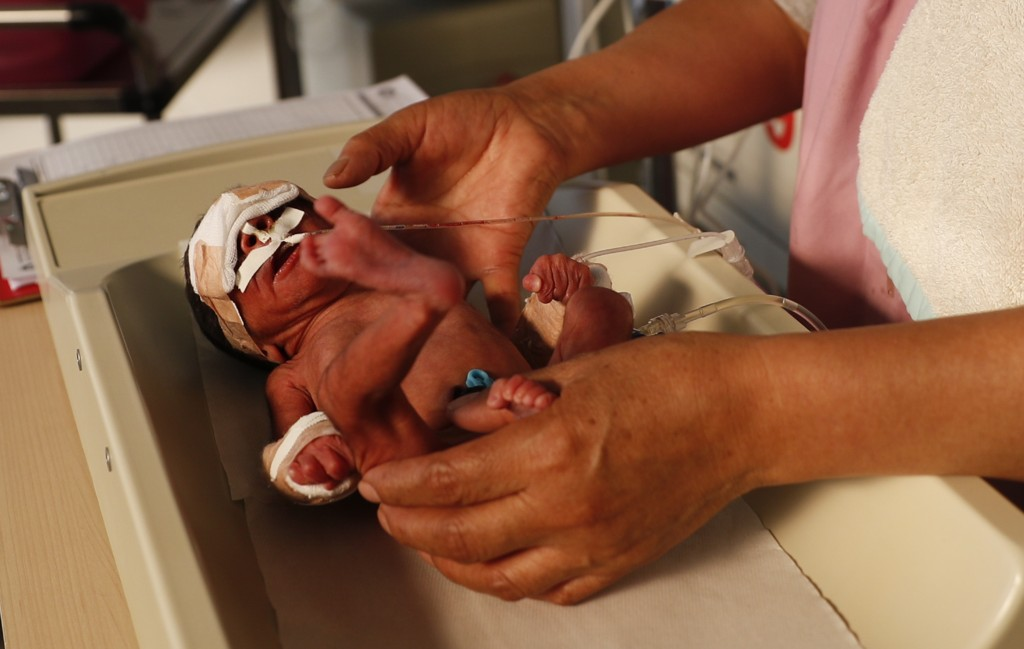 A nurse attends to a newborn baby in the intensive care unit of the Women's Hospital maternity ward in La Paz, Bolivia, Thursday, Aug. 13, 2020. Docto...