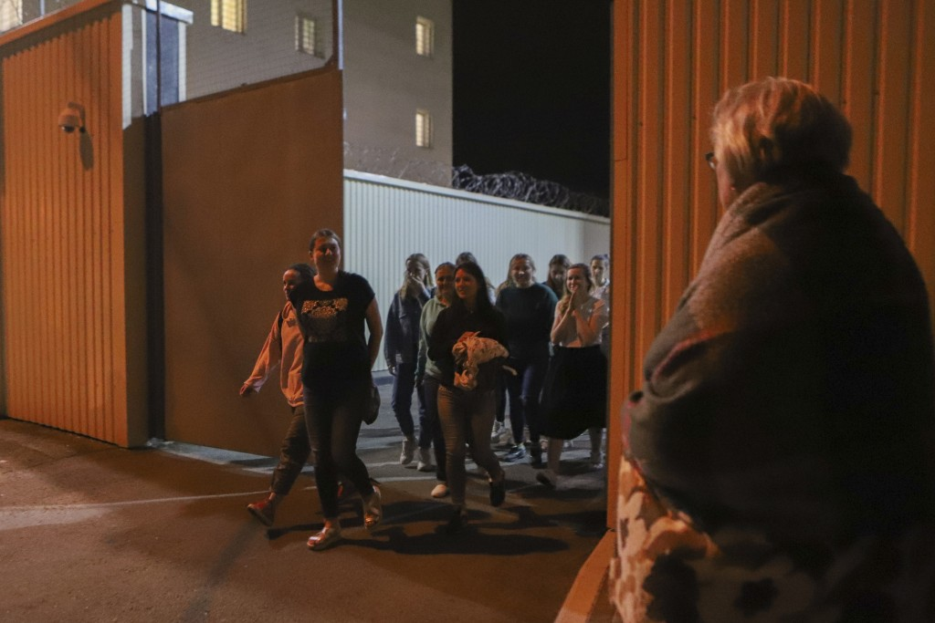 Women walk through a gate after being released from a detention center where protesters were detained during a mass rally following presidential elect...