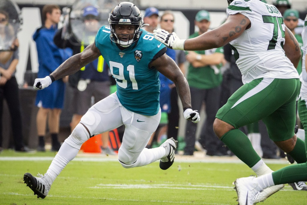 FILE - In this Oct. 27, 2019, file photo, Jacksonville Jaguars defensive end Yannick Ngakoue (91) rushes New York Jets quarterback Sam Darnold (14) du...