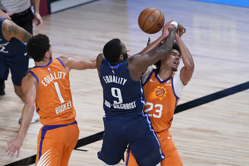 Dallas Mavericks' Michael Kidd-Gilchrist (9) reaches for a rebound between Phoenix Suns' Devin Booker (1) and Cameron Johnson (23) during the second h...