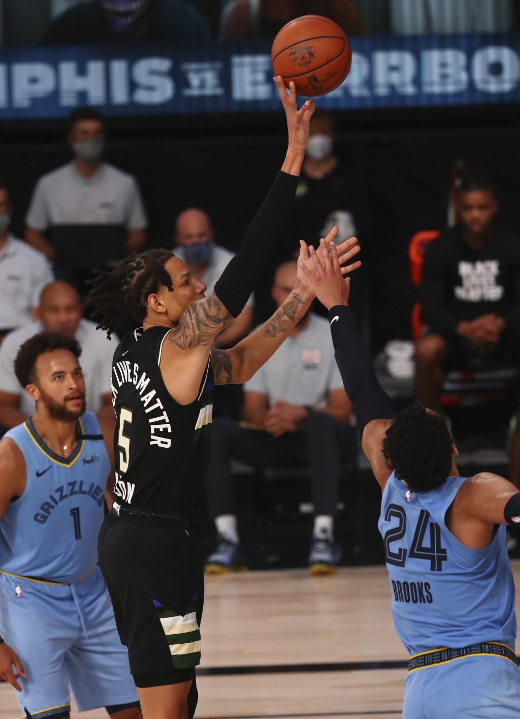Milwaukee Bucks forward D.J. Wilson (5) shoots against Memphis Grizzlies guard Dillon Brooks (24) in the second half of an NBA basketball game Thursda...