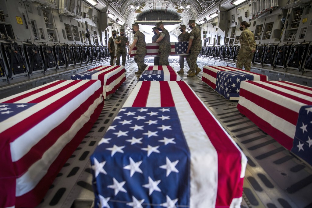 In this photo provided by the U.S. Marine Corps, U.S. Marines and sailors carry a casket inside a U.S. Air Force C-17 Globemaster III at Marine Corps ...