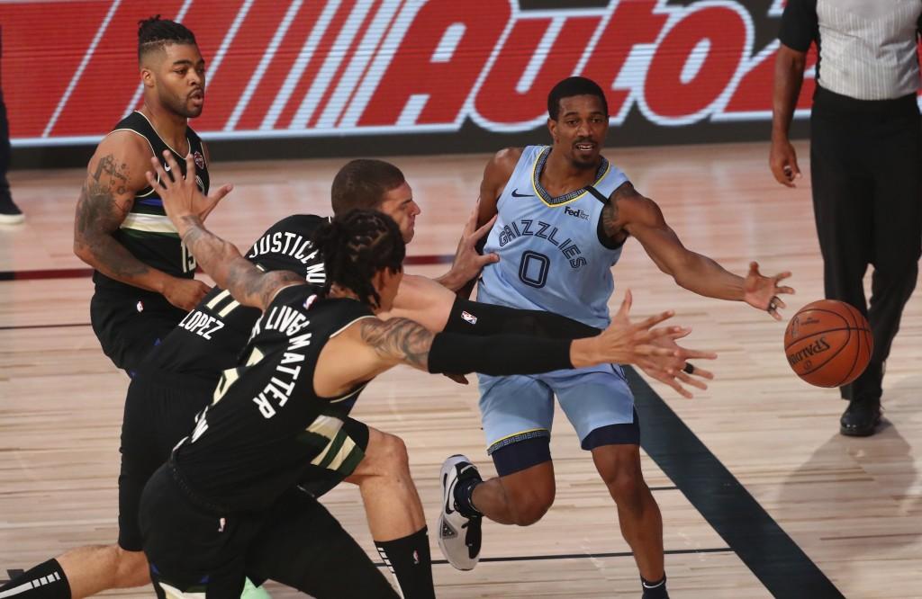 Memphis Grizzlies guard De'Anthony Melton (0) passes against Milwaukee Bucks center Brook Lopez (11) and forward D.J. Wilson (5) during an NBA basketb...