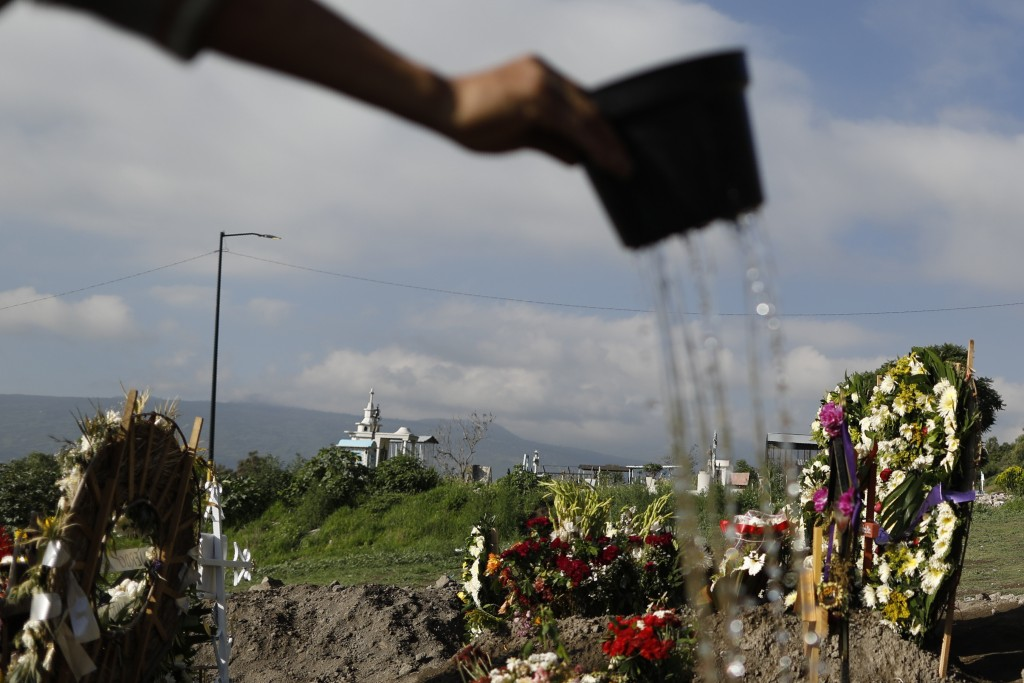 Cemetery worker Gerardo Felipe waters graves planted with grass and flowers, in a section of the Municipal Cemetery of Valle de Chalco that opened thr...