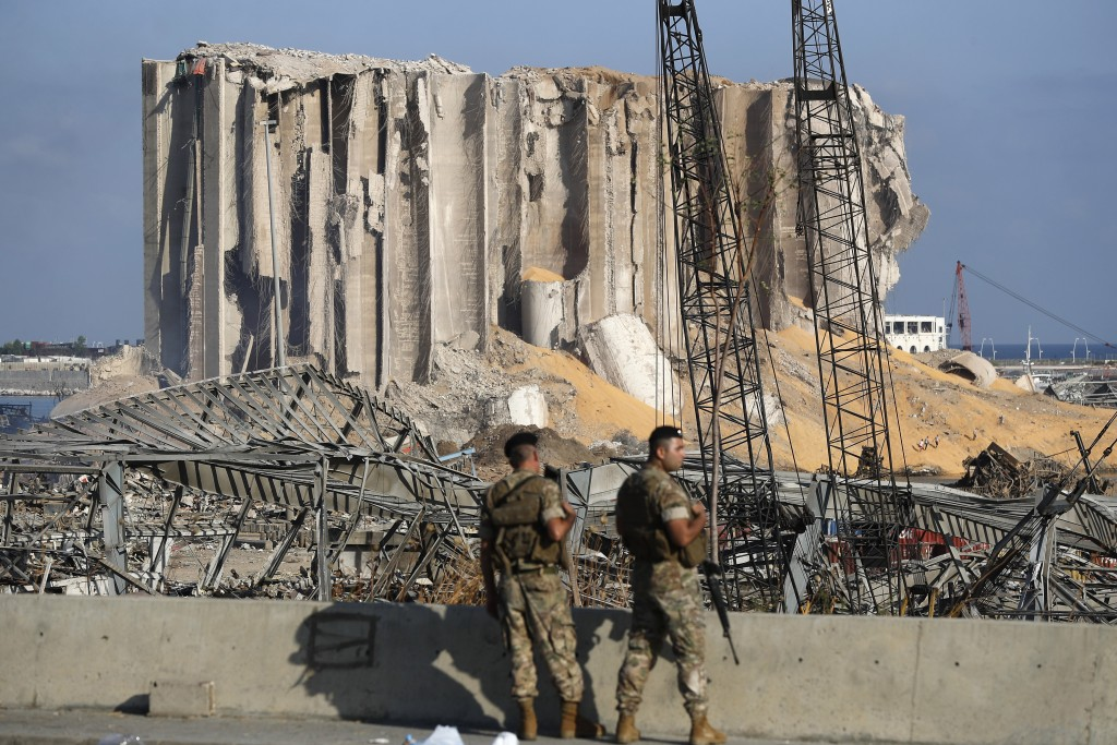 FILE - In this August 6, 2020 file photo, Lebanese army soldiers stand guard at the scene where an explosion hit on Tuesday the seaport of Beirut, Leb...