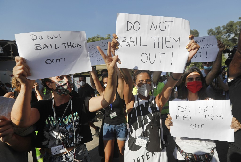 FILE - In this Aug. 13, 2020 file photo, NGO volunteers hold up placards against Lebanese politicians, as they protest during the visit of U.S. Unders...