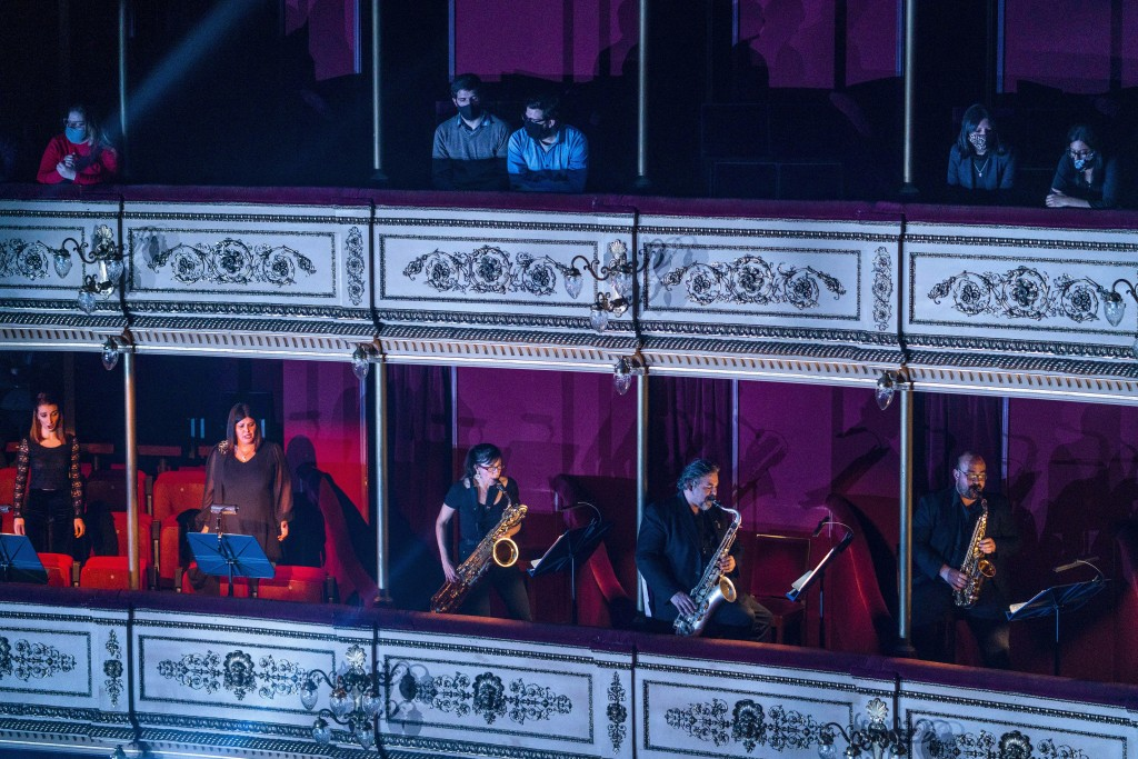 People wearing face masks amid the new coronavirus pandemic listen as musicians of the Montevideo Symphonic Band perform below them at the Solis theat...