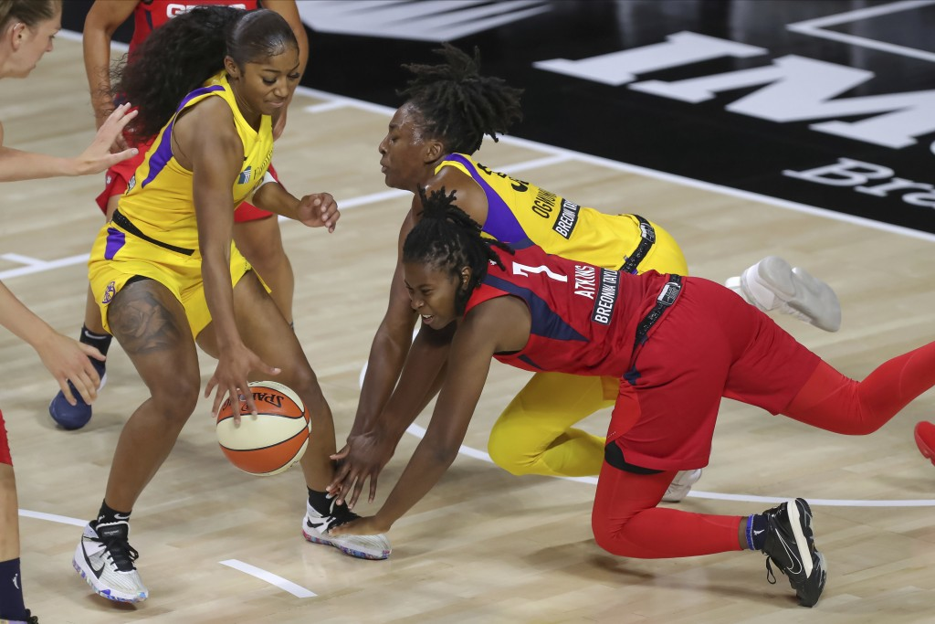 Los Angeles Sparks' Te'a Cooper, left, grabs a loose ball as Washington Mystics' Ariel Atkins (7) and Nneka Ogwumike dive for it during the first half...