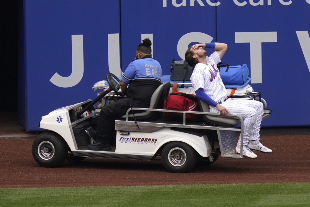 New York Mets left fielder Jeff McNeil reacts as he rides a cart off the field after being injured during the first inning of a baseball game against ...