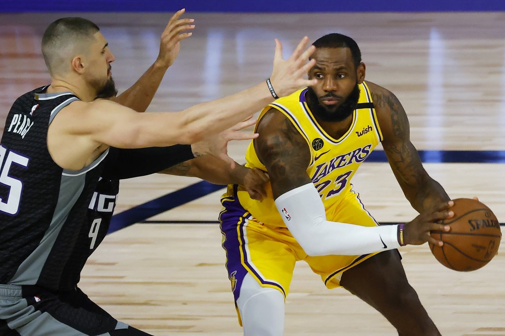 Los Angeles Lakers' LeBron James (23) is pressured by Sacramento Kings' Alex Len (25) during the first half of an NBA basketball game Thursday, Aug. 1...