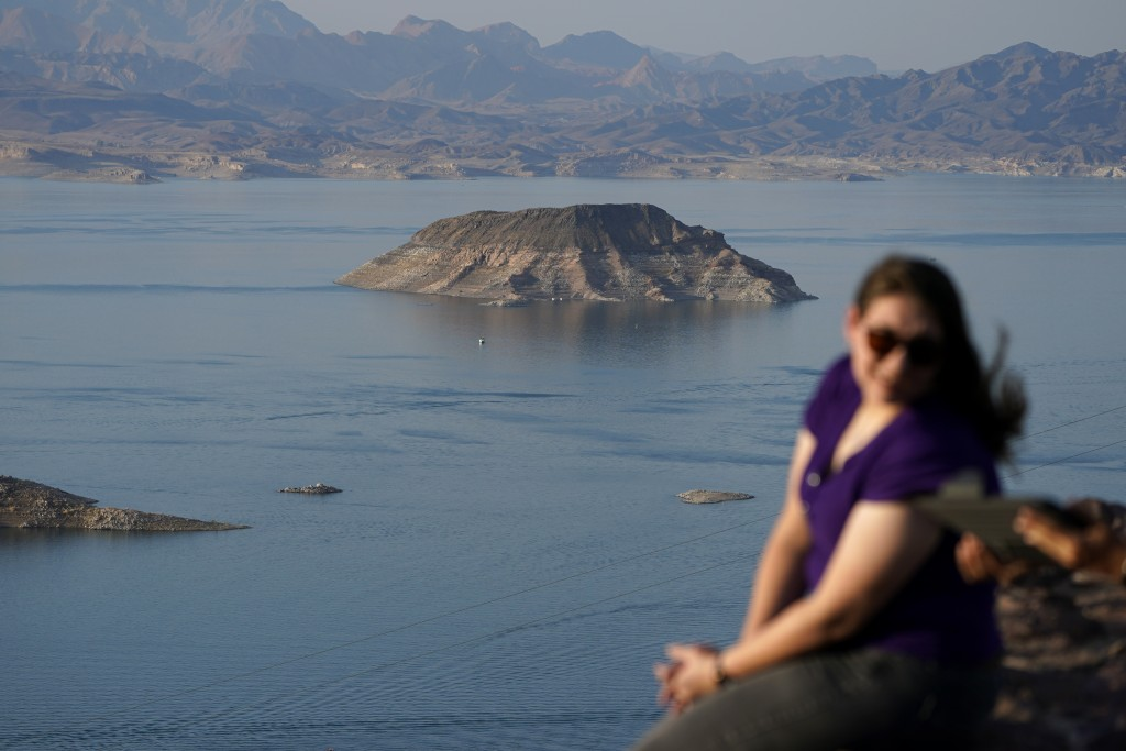 People sit on an overlook on Lake Mead at the Lake Mead National Recreation Area, Thursday, Aug. 13, 2020, near Boulder City, Nev. The U.S. Bureau of ...