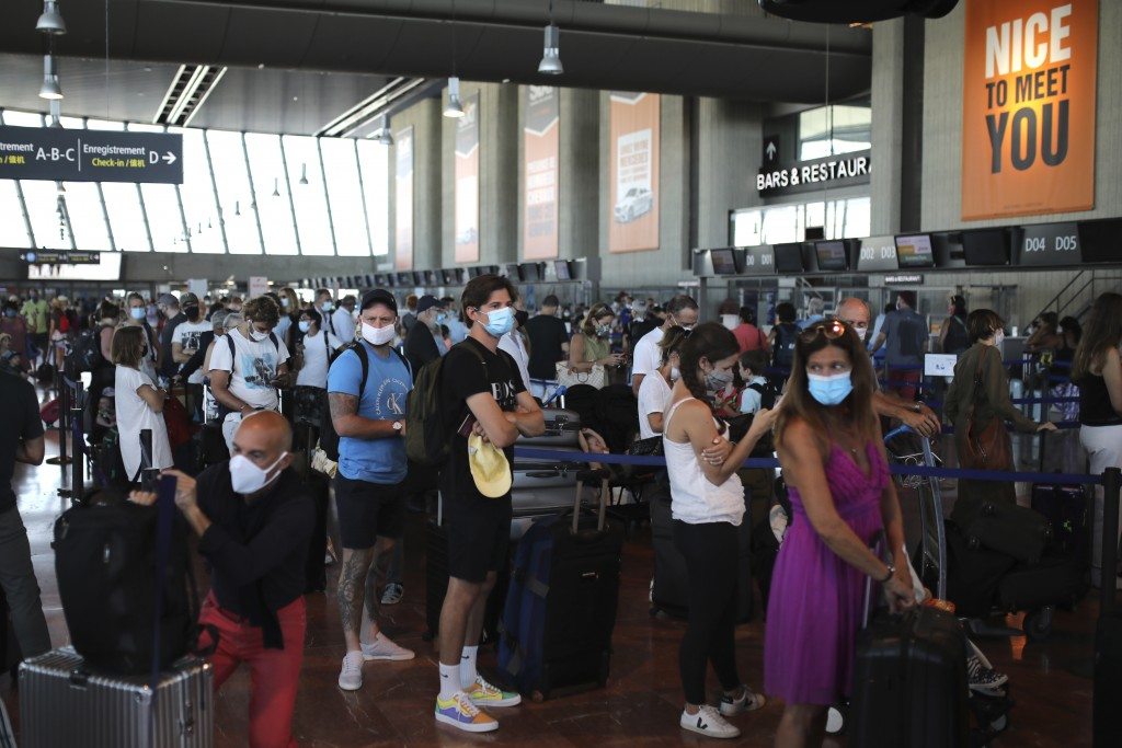 People queue in line to check-in for a British Airways flight to Heathrow airport, Friday Aug.14, 2020 at Nice airport, southern France. British holid...