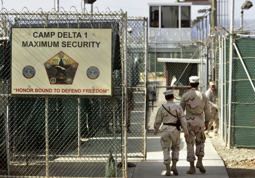 FILE - In this June 27, 2006, file photo, reviewed by a U.S. Department of Defense official, U.S. military guards walk within Camp Delta military-run ...