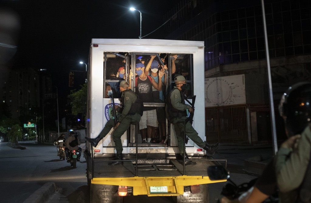 Men who were detained for not complying with COVID-19 regulations by breaking curfew or attending block parties, are transported in a police van to a ...