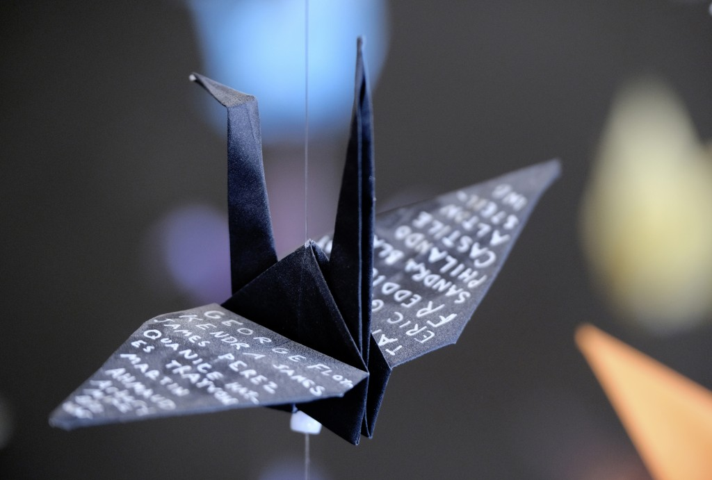 An origami paper crane with the names of victims of police violence hangs with thousands of other cranes in an exhibit for those who have died in the ...