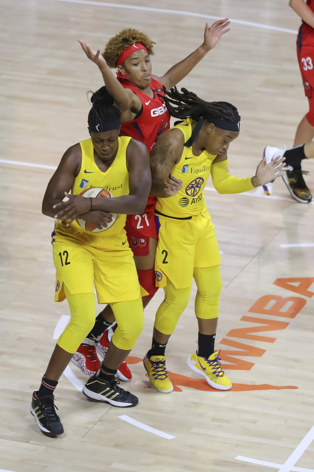 Los Angeles Sparks' Chelsea Gray (12) steals a pass intended for Washington Mystics' Tianna Hawkins (21) as Sparks' Riquna Williams (2) defends during...