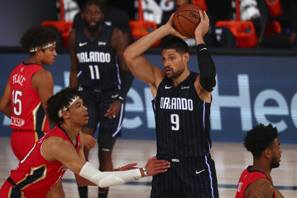 Orlando Magic center Nikola Vucevic (9) controls the ball against New Orleans Pelicans center Jaxson Hayes, front left, during the first half of an NB...