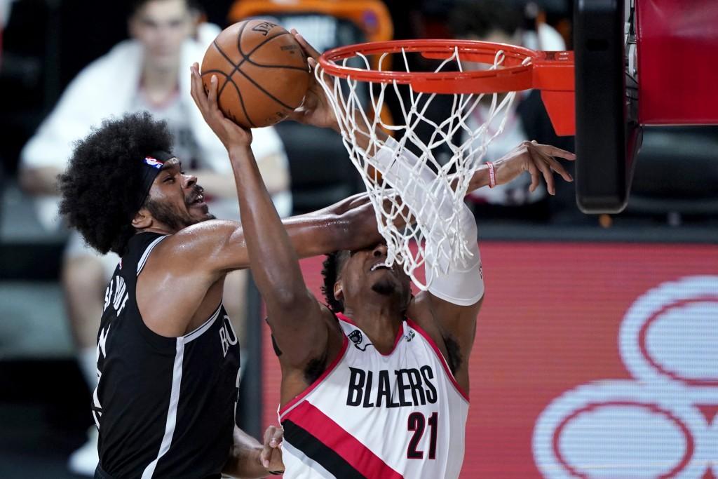 Brooklyn Nets' Jarrett Allen, left, fouls Portland Trail Blazers' Hassan Whiteside during the first half of an NBA basketball game Thursday, Aug. 13, ...