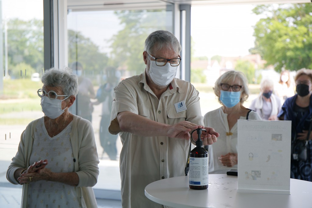 Visitors use hand gel, during the reopening of the Louvre Museum in Lens, northern France, Wednesday, June 3, 2020, as  restrictions in place to contr...