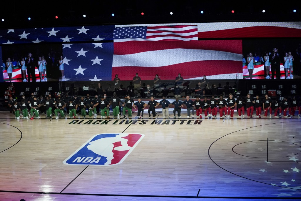 Members of the Boston Celtics and Washington Wizards kneel before the start of an NBA basketball game Thursday, Aug. 13, 2020 in Lake Buena Vista, Fla...