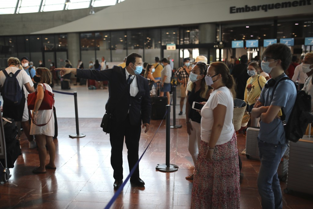 An airport employee directs people for check-in for a British Airways flight to Heathrow airport, Friday Aug.14, 2020 at Nice airport, southern France...