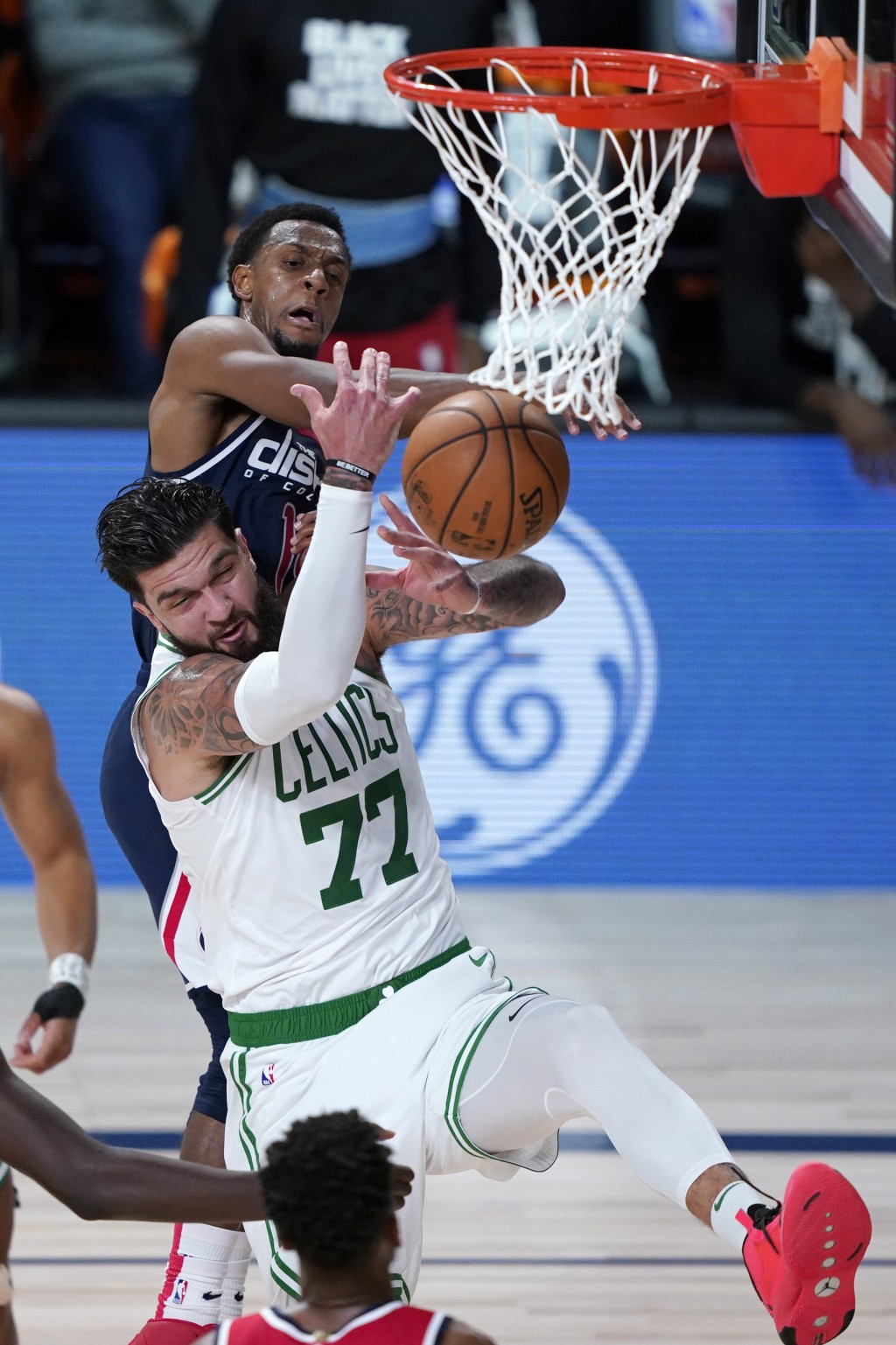 Boston Celtics' Vincent Poirier (77) and Washington Wizards' Ish Smith (14) reach for a ball during the second half of an NBA basketball game Thursday...