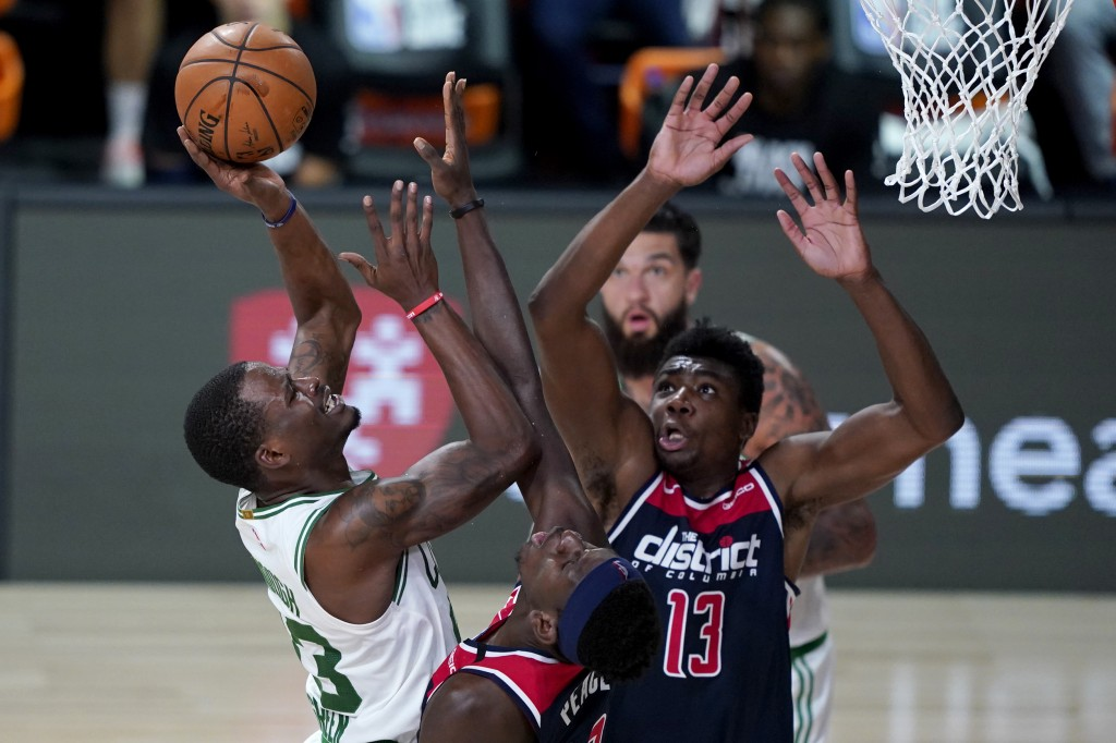 Boston Celtics' Javonte Green, left, heads to the basket past Washington Wizards' Isaac Bonga and Thomas Bryant (13) during the second half of an NBA ...
