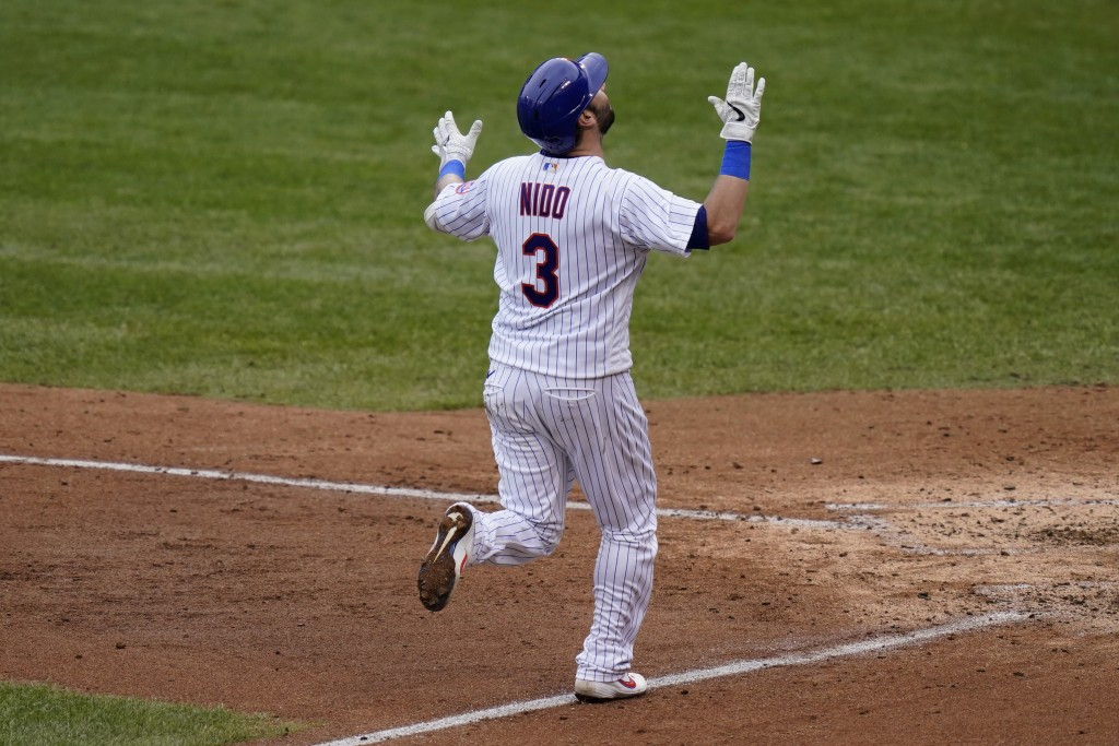 New York Mets' Tomás Nido reacts as he approcahes home plate after hitting a grand slam during the fifth inning of a baseball game against the Washing...