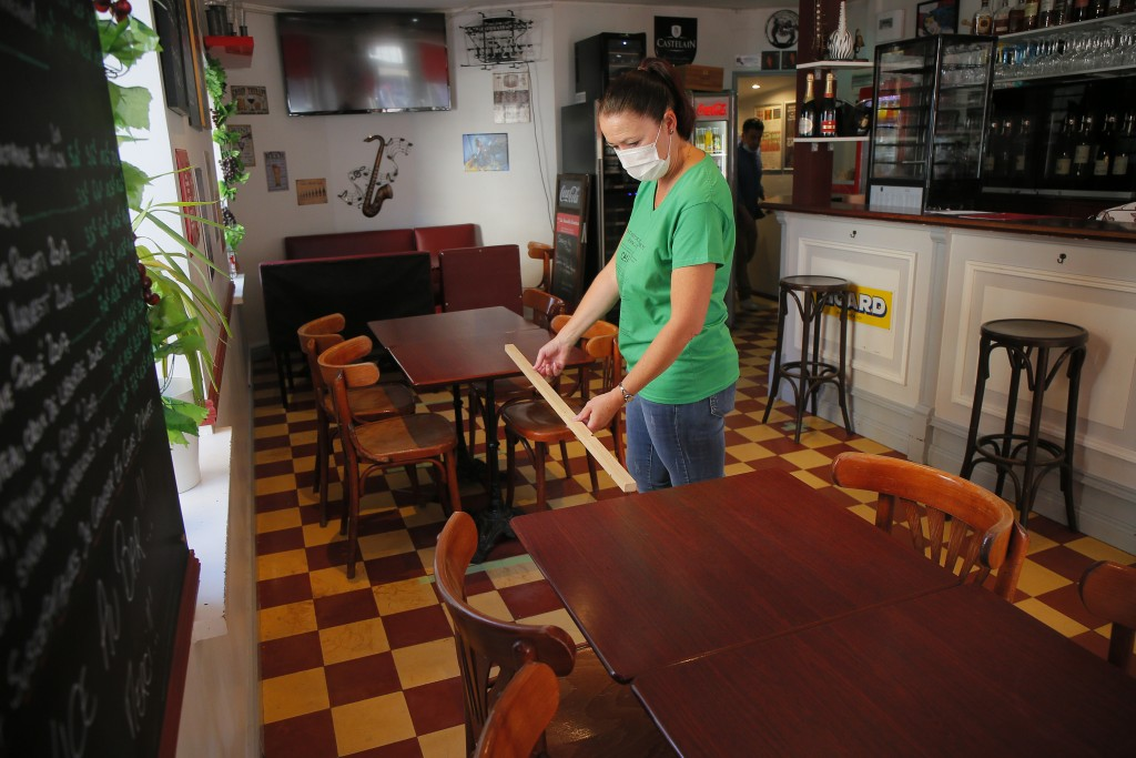A woman measures the distance between table in a restaurant of Lille, northern France, Tuesday June 2, 2020. The French way of life resumes Tuesday wi...