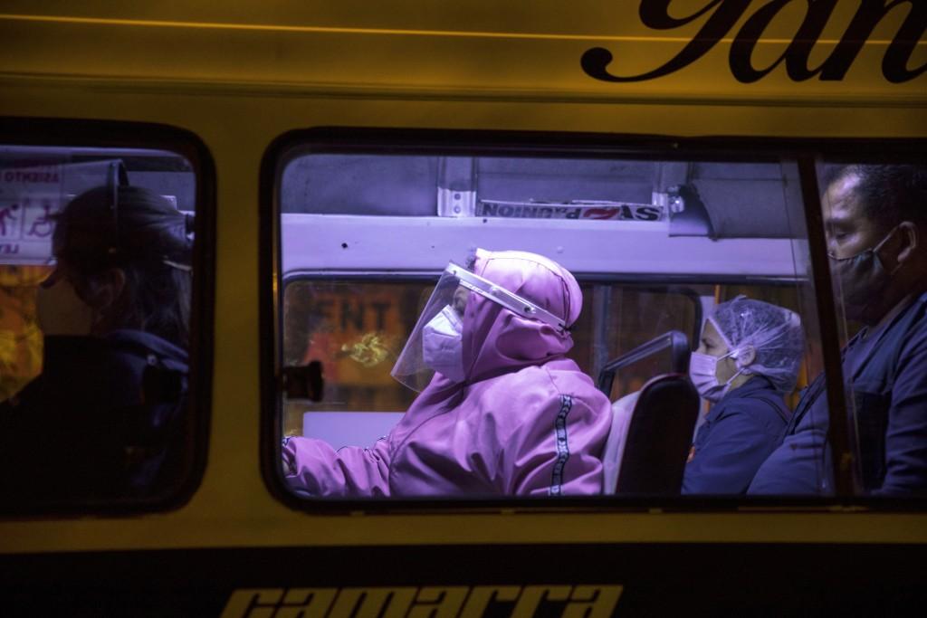 Commuters using protective gear amid the coronavirus pandemic sit inside a public bus in Lima, Peru, Thursday, Aug. 13, 2020. (AP Photo/Rodrigo Abd)