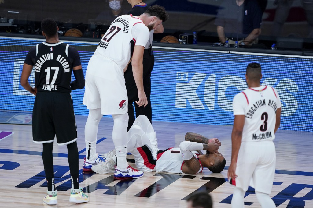 Portland Trail Blazers' Damian Lillard, bottom, reacts after being fouled by Brooklyn Nets' Garrett Temple (17) during the second half of an NBA baske...