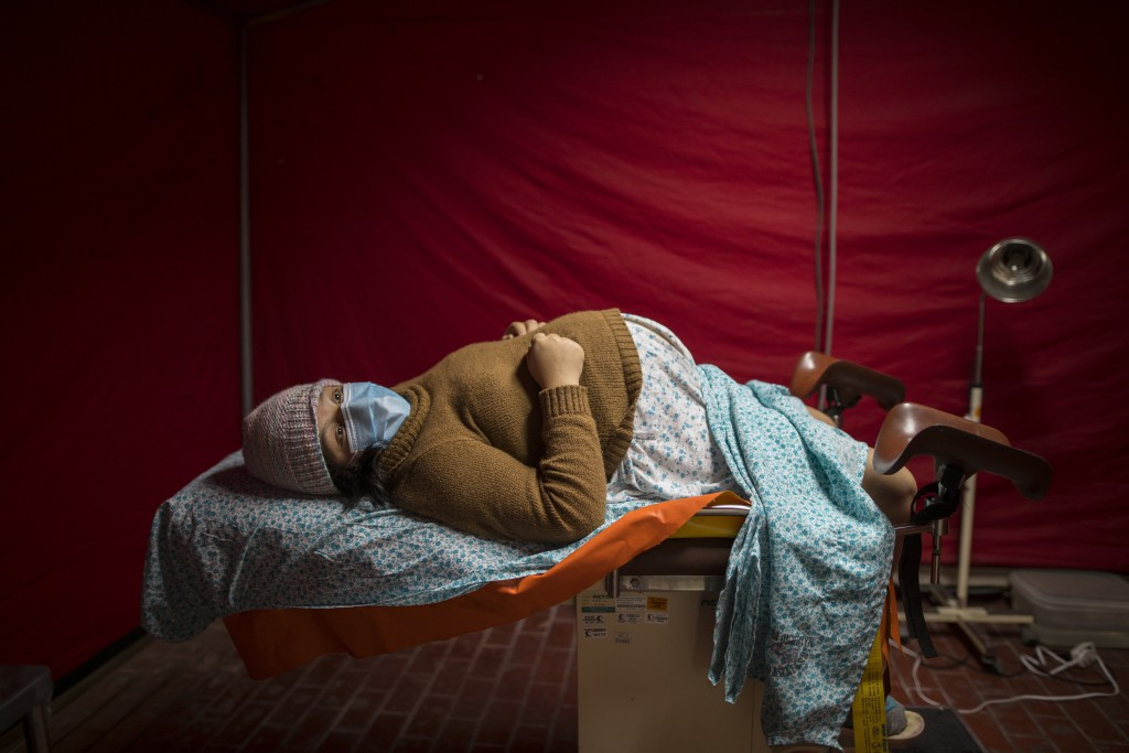 Olinda Tafur, 20, lies on an examination table as she waits to be seen by obstetrician Dr. Osvaldo Sierra inside a tent set up in the emergency area o...