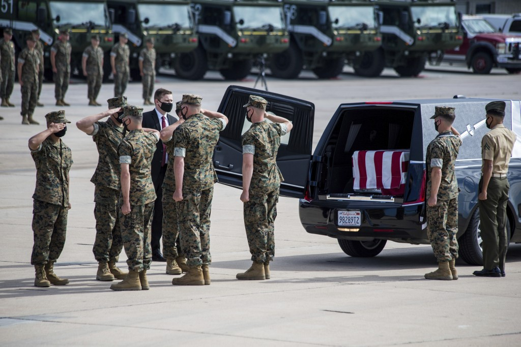 U.S. Marines and sailors salute before removing a casket to be placed aboard a U.S. Air Force C-17 Globemaster III at Marine Corps Air Station Miramar...