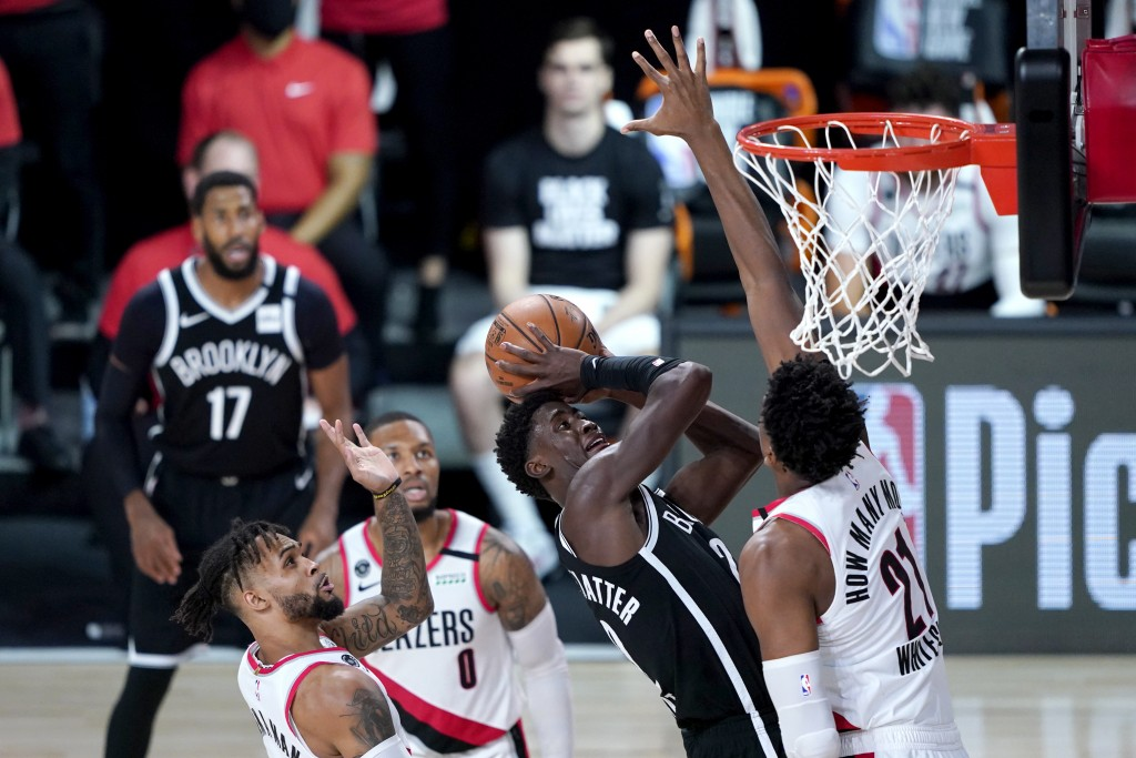 Brooklyn Nets' Caris LeVert, center, goes up for a shot against Portland Trail Blazers' Hassan Whiteside (21) during the second half of an NBA basketb...