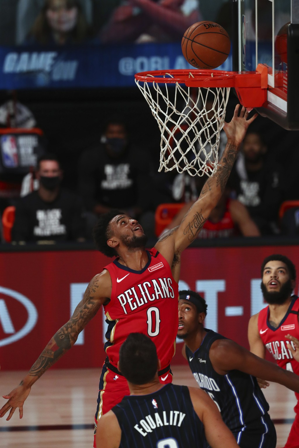 New Orleans Pelicans guard Nickeil Alexander-Walker (0) shoots a layup over Orlando Magic center Nikola Vucevic, foreground, during the first half of ...