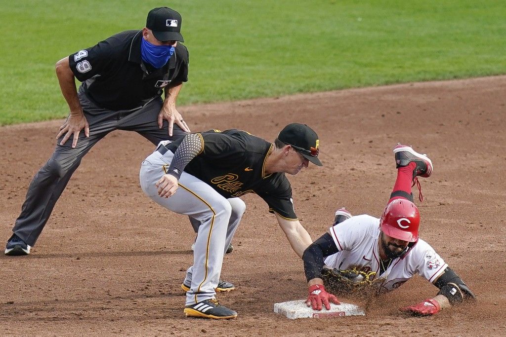 Cincinnati Reds' Nicholas Castellanos, right, slides safely into second base while avoiding the tag of Pittsburgh Pirates shortstop Kevin Newman, cent...