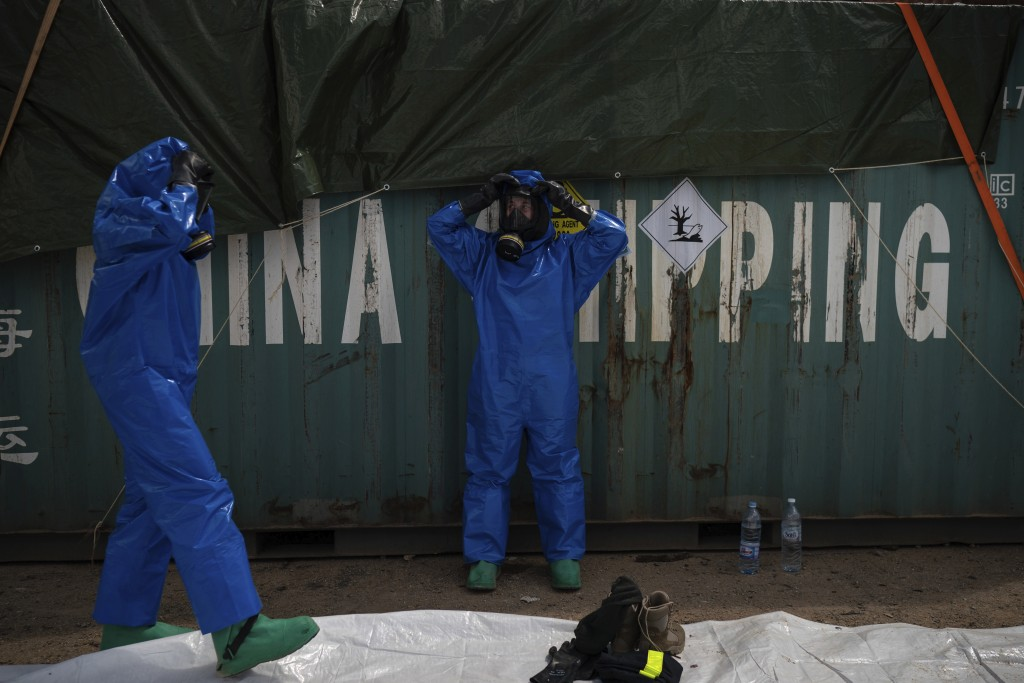 FILE - In this August 10, 2020 file photo, French emergency workers, part of a special unit working with chemicals, suit up near the site of last week...