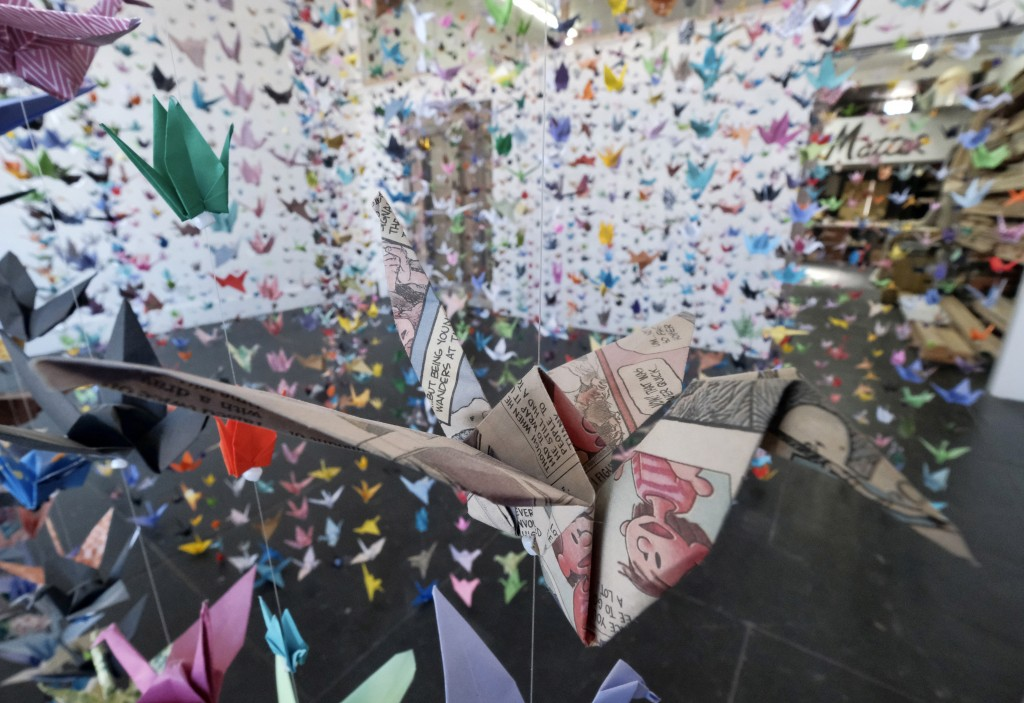 An origami crane made from a newspaper comic strip hangs with thousands of others during a memorial exhibit for the victims of COVID-19 at the Matter ...