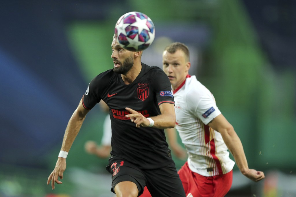 Atletico Madrid's Yannick Carrasco, left, challenges for the ball with Leipzig's Lukas Klostermann during the Champions League quarterfinal match betw...